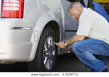 Side view of a male mechanic inflating car's tire
