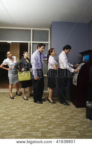 Impatient business people standing in a queue at an ATM