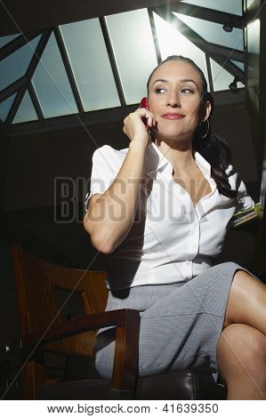 Beautiful business woman talking on mobile phone while sitting on chair at office