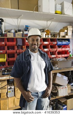 Portrait of a happy industrial worker wearing hardhat at workplace