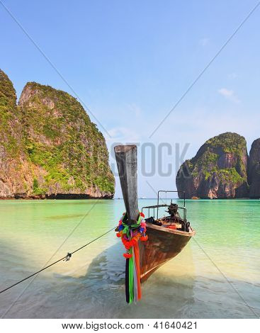 Scenic green islands of Thailand coast. Emerald sea and fine white sand. Moored on the beach tourist boat, decorated with red silk scarf and a flower wreath