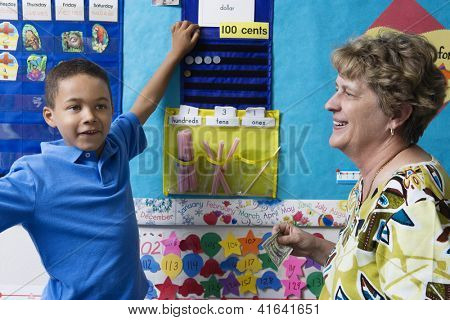Preadolescent boy learning mathematics with teacher in classroom