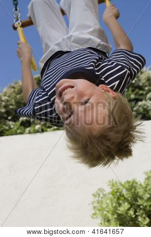 A preadolescent A preadolescent boy enjoying while hanging upside down on a swing