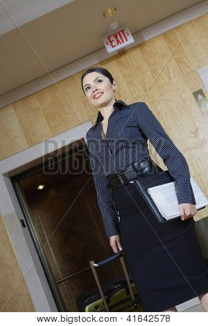 Low angle view of a happy business woman pulling trolley against elevator