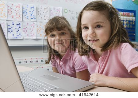 Preadolescent girls studying from laptop in the classroom