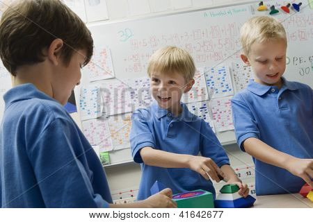 Three happy preadolescent boys solving puzzle game in a playschool