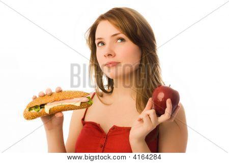 Beautiful Girl Choosing Between An Apple And Hot Dog