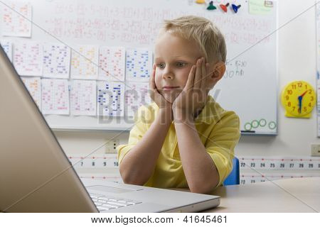 Preadolescent boy looking at laptop against whiteboard in classroom