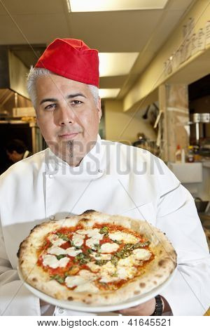 Portrait of a confident chef wearing headgear while holding pizza in commercial kitchen