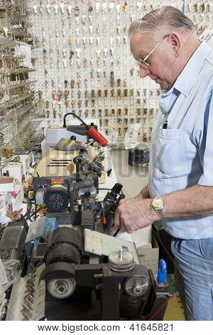 Vista lateral de cerrajería trabajando en el almacén de claves