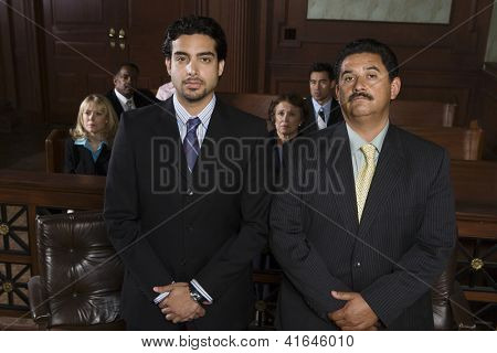 Portrait of a middle aged advocate standing with client and people in the background