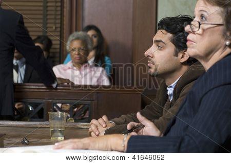 Vista lateral dos defensores com cliente durante o julgamento no Tribunal