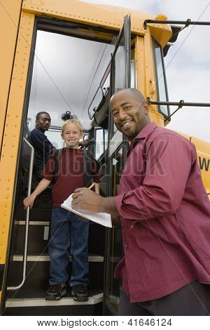 Low angle view of man writing on paper while boy getting down from school bus
