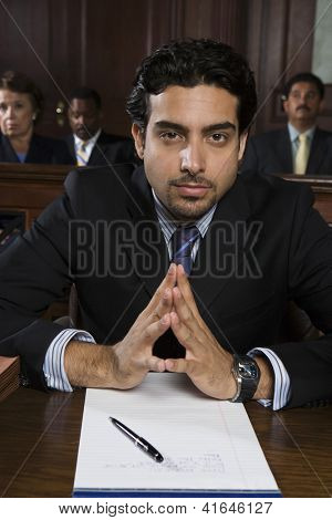 Portrait of a young confident male advocate sitting with people in the background