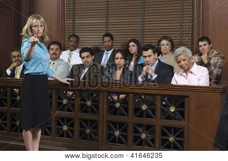 Portrait of a female advocate pointing with jurors sitting together in the witness stand at court house
