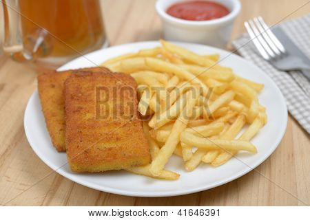 Fish and chips on a table with tomato sauce and beer