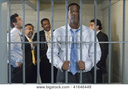 Portrait of an unhappy businessman in jail holding bars with colleagues in the background