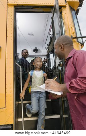 Little girl looking at man while getting down from school bus with driver sitting in background