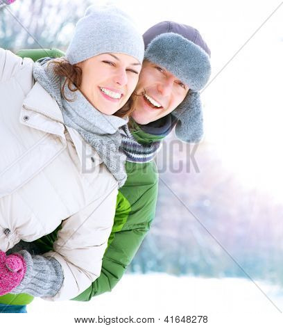 Casal feliz se divertindo ao ar livre. Neve. Férias de Inverno. Ao ar livre