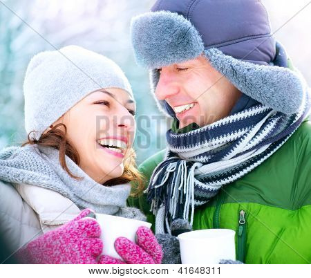 Happy Couple Having Fun Outdoors. Snow. Winter Vacation. Hot Drink Outdoor. White Teeth