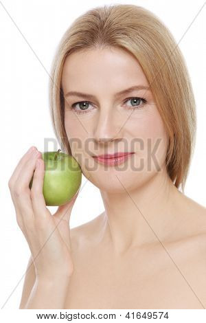 Portrait of beautiful mature woman with clear skin and green apple in her hand, on white background