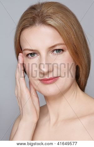 Portrait of attractive mature woman with clean skin touching her face