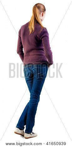 back view of standing young beautiful  blonde woman. girl in jeans and sweater watching. Rear view people collection.  backside view of person.  Isolated over white background.