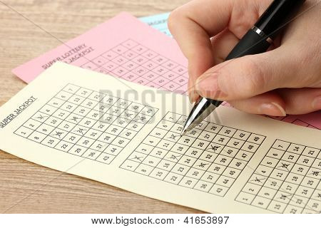 Closeup of lotto ticket during the marking of numbers, on wooden background