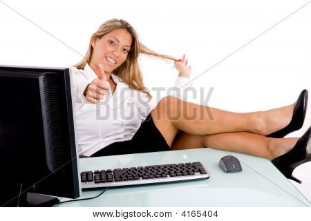 Front View Of Smiling Businesswoman Showing Thumb Up In Office