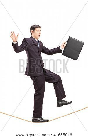 Full length portrait of a businessman with briefcase walking on a rope isolated on white background