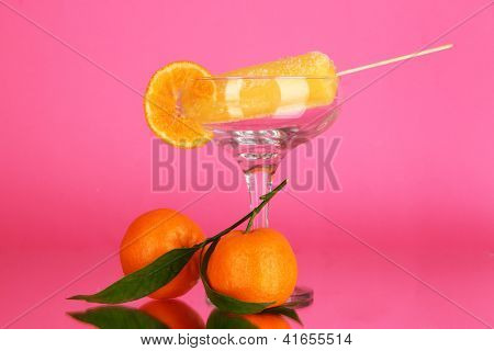 Yellow fruit juice ice in vase on pink background