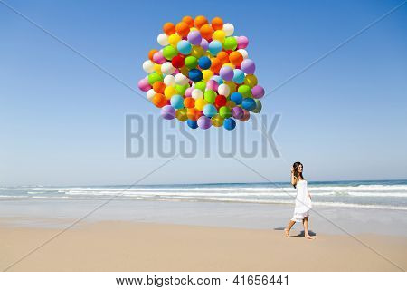 Beautiful girl walking in the beach holding dozens of colored balloons