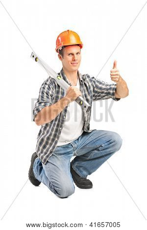 A smiling worker holding a construction bubble level and giving thumb up isolated on white background