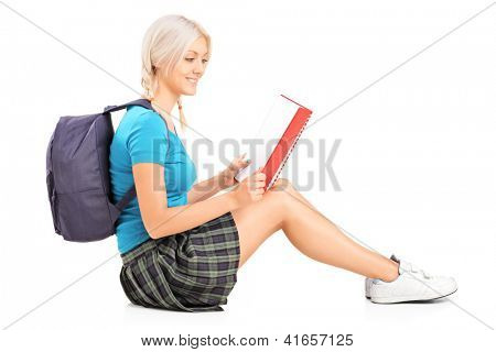 A smiling student reading a book and sitting on a floor isolated on white background