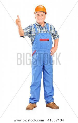 Full length portrait of a male worker with helmet giving a thumb up isolated on white background