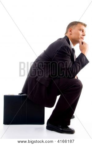 Handsome Young Executive In Deep Thought Sitting On His Briefcase