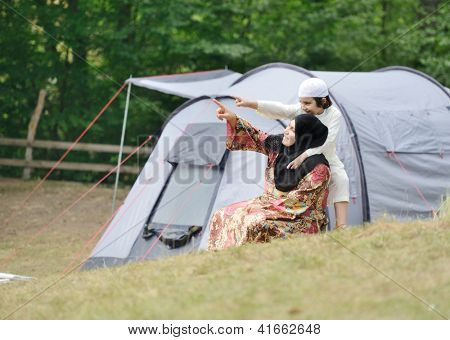Muslim Arabic woman with her son camping in nature