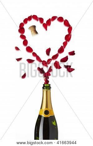 Bottle Of Champagne Popping Red Rose Petals With Cork Into The Air
