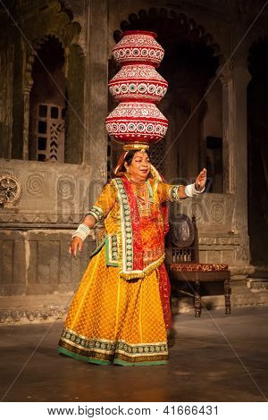 UDAIPUR, INDIA - NOVEMBER 24: Bhavai performance - famous folk dance of Rajasthan state of India. Performer balances number of earthen pots as she dance. November 24, 2012 in Udaipur, Rajasthan, India