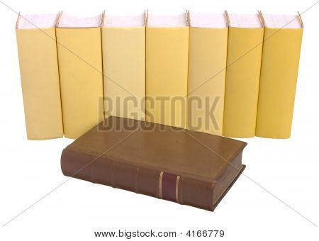 Row Of Yellow Books With An Old Leather Bound Book