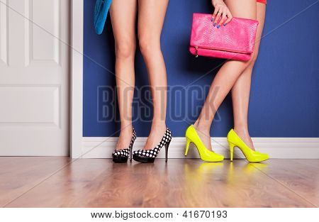 Two girls wearing high heels waiting at the door