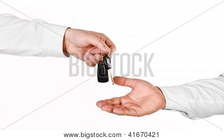 Male Hand Holding A Car Key And Handing It Over To Another Person