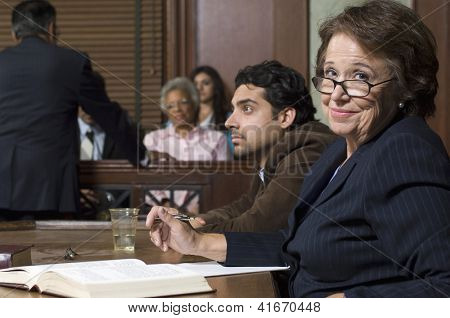 Portrait of a happy senior advocate sitting with client during prosecution in court house