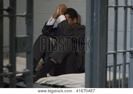 Full length of a depressed businessman sitting in jail
