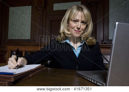 Portrait of a happy lawyer writing notes with laptop in the foreground