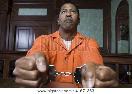 Prisioneiro americano Africano restringido com algemas sentado na sala de audiências
