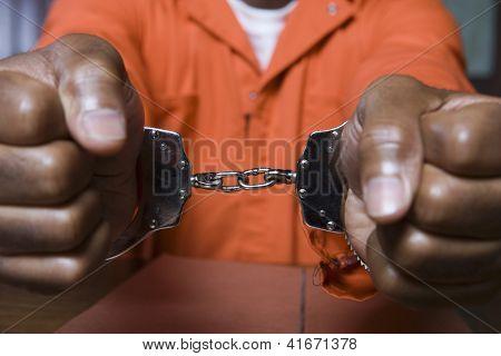Close-up de uma mão de prisioneiro restringida com algemas