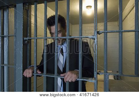 A business man standing behind bars