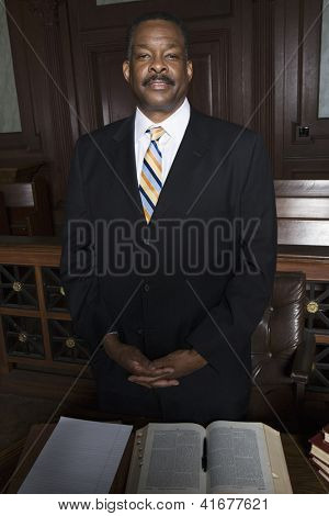Portrait of African American advocate standing with books on table in courthouse