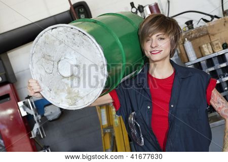 Portrait of a happy young female mechanic carrying oil drum on shoulder in car workshop